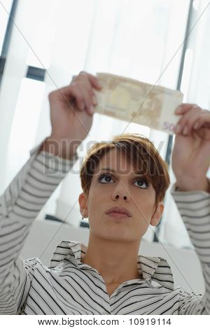 Woman Checking Banknote Watermark