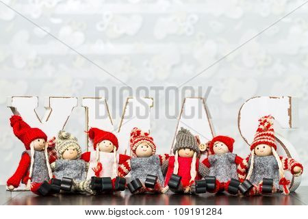 White Wooden Letters On Brown Wooden Table Forming Word Xmas With Ribbons And Red People Figures Sit