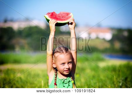 Small girl holding slice of watermelons on lawn