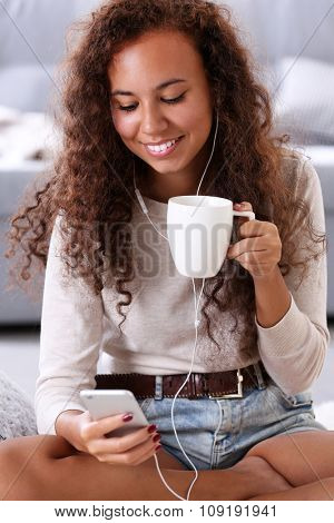 Beautiful girl listening music by headphones with cup of coffee in hands