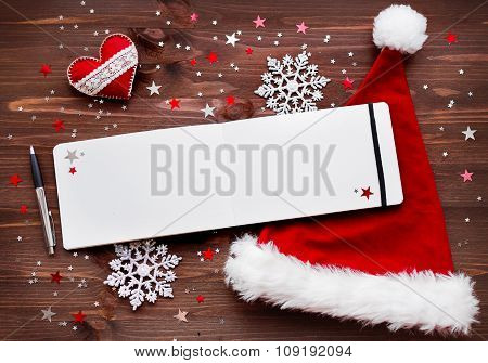 Christmas And New Year Background With Felt Heart, Red Santa's Hat, Notepad With Pen And Decorations