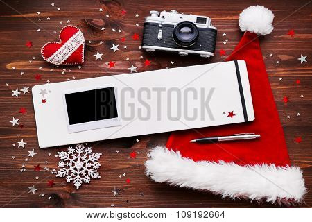 Christmas And New Year Background With Old Camera, Santa's Hat, Notepad With Pen, Photo