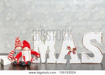 White Wooden Letters On Brown Wooden Table Forming Word Xmas With Ribbons And Red Figures Around The