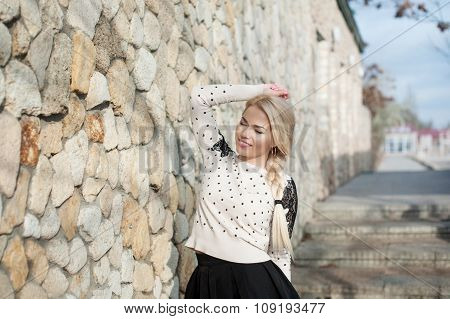 Young woman standing near the stone walls.