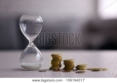 Hourglass with coins on table on bright background