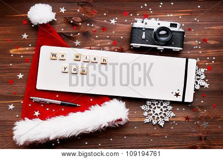 Christmas And New Year Background With Old Fashioned Camera, Red Santa's Hat, Notepad With Pen