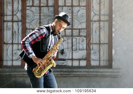 Young man plays saxophone on urban background