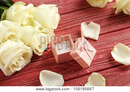 Bouquet Of White Roses With Ring On Red Wooden Background