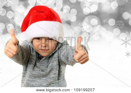 Five year old boy wearing a Santa hat with both thumbs up on a snowflake background.