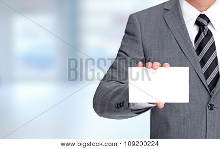 Businessman with a business card over blue background.