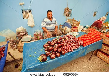 Happy Vegetable Trader Waiting For Customers With Eggplant And Tomatoes On Rural Market In Turkey