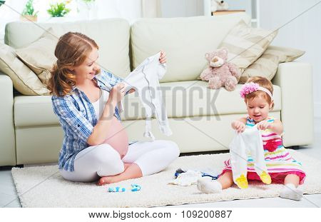 Happy Family Pregnant Mother And Child Daughter Preparing Clothing For Newborn Baby