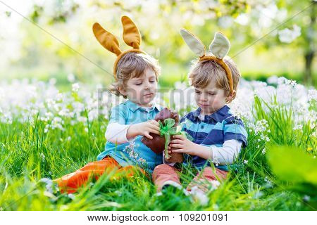 Two little kids playing with Easter chocolate bunny outdoors