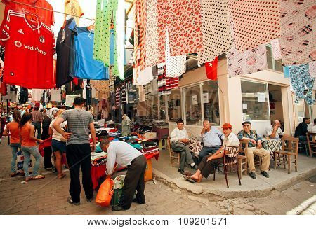Old Market And Many Seniors Sitting And Talking At Street Cafe Of Turkish Village