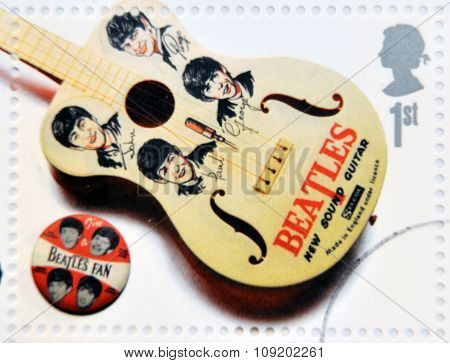A stamp printed in Great Britain shows the Beatles memorabilia (guitar and pin)