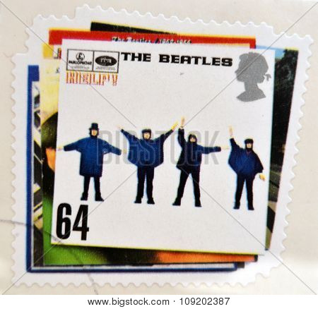 a postage stamp printed in Great Britain showing an image of The Beatles Help album cover