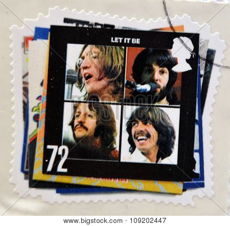 a postage stamp printed in Great Britain showing an image of The Beatles Let It Be album cover