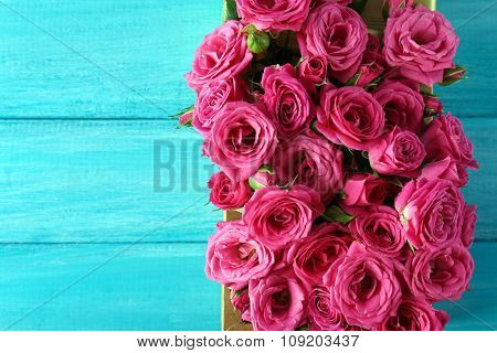 Beautiful roses in box on wooden background