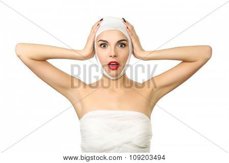 Young emotional woman with a gauze bandage on her head and nose, isolated on white