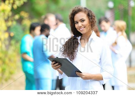 Attractive young woman doctor with clipboard in hands against group of medics, outdoors