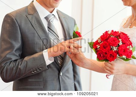 Bride wearing the ring to groom. Wedding rings exchange.