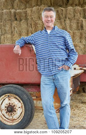 Farmer Standing In Front Of Straw Bales And Old Farm Equipment