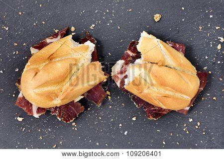 high-angle shot of a spanish bocadillo de jamon serrano, a serrano ham sandwich, cut in half on a slate stone background