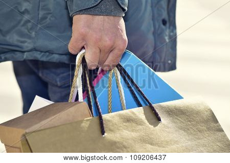 closeup of a young caucasian man carrying some different paper shopping bags in the street
