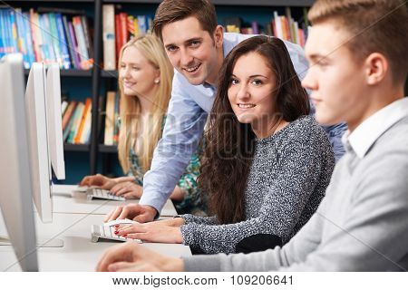 Tutor Helping Students Working At Computer