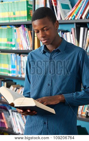 Male Teenage Student Reading Book In Library