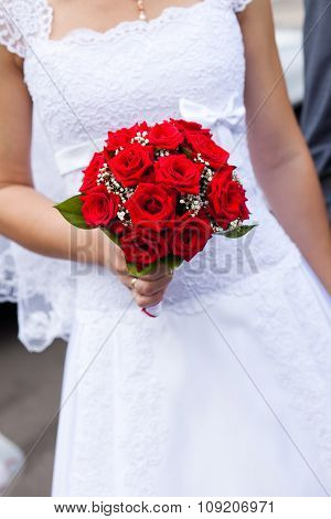 red wedding bouquet in bridal hands
