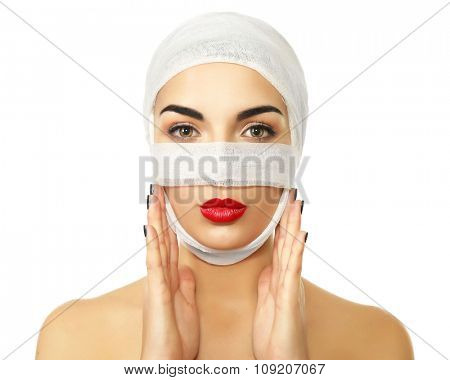 Young beautiful woman with a gauze bandage on her head and nose, isolated on white, close-up