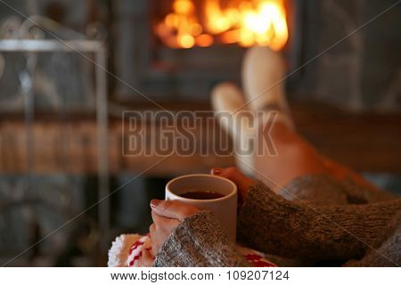 Woman resting with cup of hot drink near fireplace