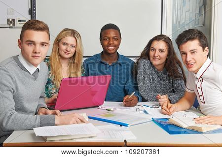 Group Of Teenage Pupils Working Together In Classroom