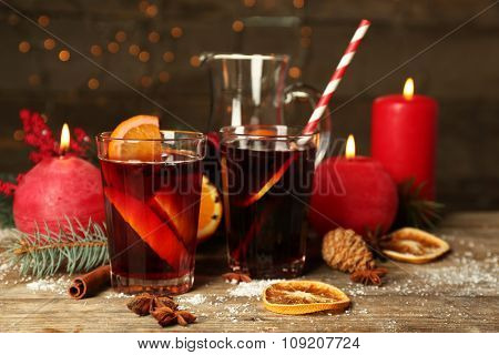 Decorated composition of mulled wine in glasses on wooden table