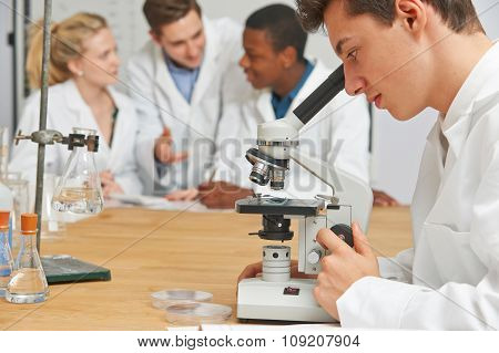 Male Pupil Using Microscope In Science Class