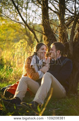 Young Couple Sitting And Laughing Near The Tree In The Forest
