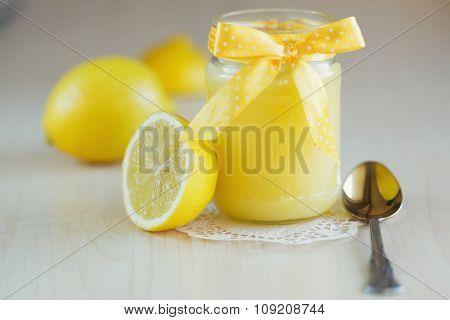 A homemade jar of lemon curd with a lemon and spoon