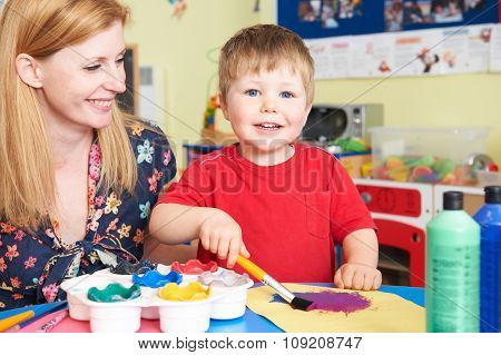 Teacher Helping Pre School Pupil In Art Class
