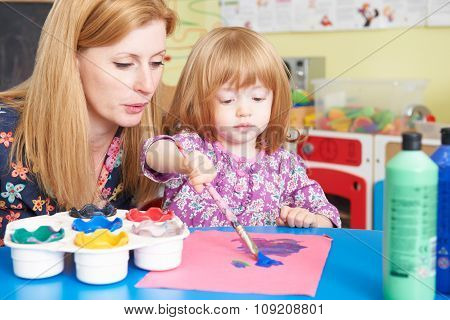 Teacher Helping Pre School Child In Art Class