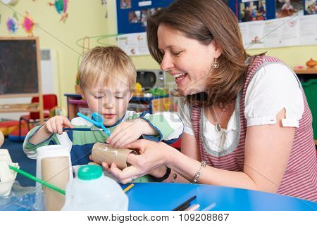 Teacher Helping Little Boy To Build Model In Art Class