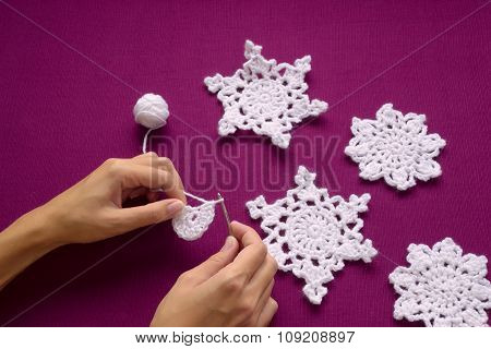 Woman Knits Christmas Decoration - Snowflakes