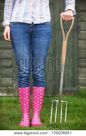 Close Of Woman Wearing Pink Wellingtons Holding Garden Fork