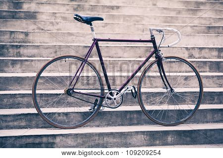 Road bicycle fixed gear bike on city concrete street. Urban industrial cycling bike on city stairs
