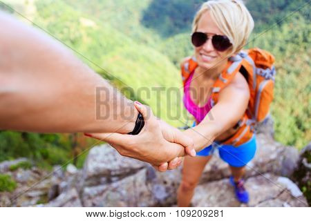 Helping hand couple hiking help each other. Man and woman teamwork climbing or hiking motivation