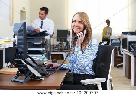 Businesswoman Taking Phone Call In Busy Office