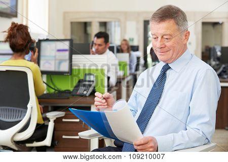 Senior Businessman In Busy Modern Office