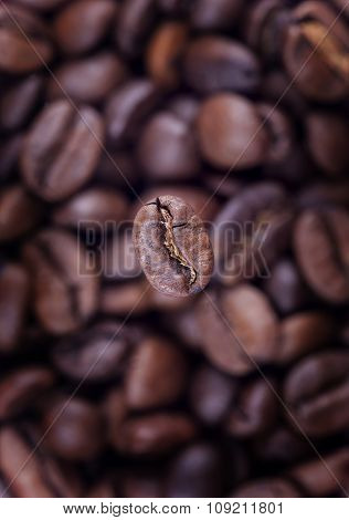 Coffee background close-up. Focus on one grain