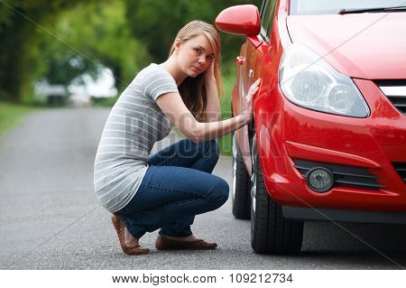 Young Female Motorist With Puncture On Country Road