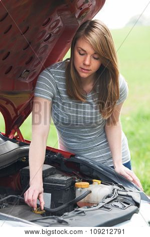 Broken Down Female Motorist Looking At Car Engine